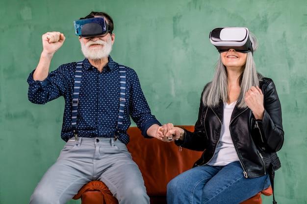 Retrato de una pareja de ancianos emocionados, sentados juntos en una silla roja cerca de la pared verde, tomados de la mano, con los puños cerrados y disfrutando de la realidad virtual con gafas virtuales