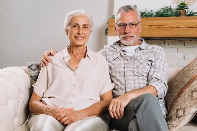 Retrato de una pareja de ancianos que se sienta en el sofá