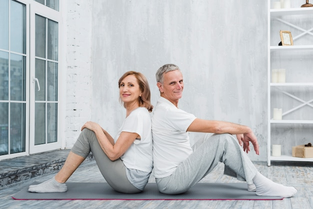 Retrato de una pareja de ancianos sentados espalda con espalda en estera de yoga