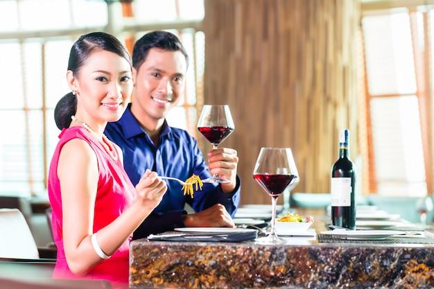Retrato de pareja asiática comiendo en el restaurante
