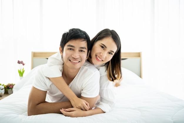 Retrato de pareja asiática divertida y romántica en el dormitorio con luz natural desde la ventana, concepto de relación entre marido y mujer y ser una familia.