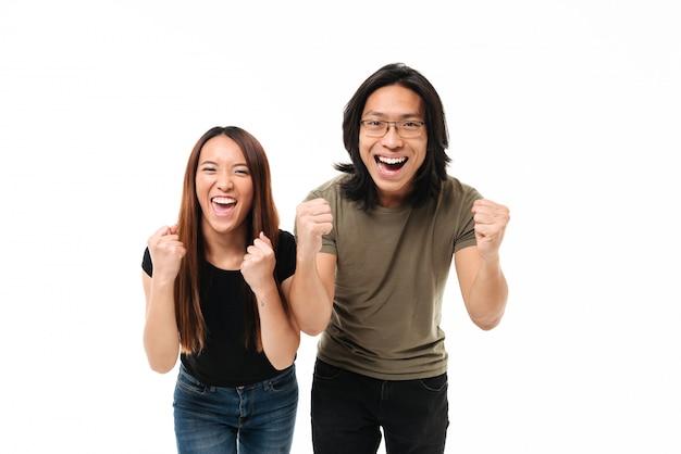 Retrato de una pareja asiática satisfecha celebrando el éxito