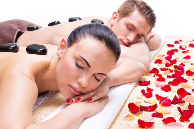 Retrato de pareja atractiva relajante en el salón de spa con piedras calientes en el cuerpo.