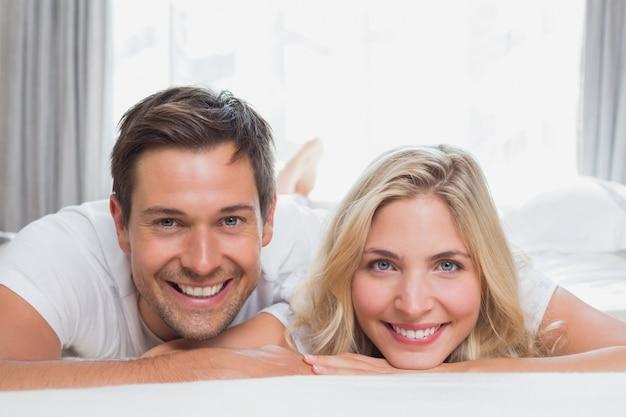Retrato de una pareja casual relajada sonriendo en la cama