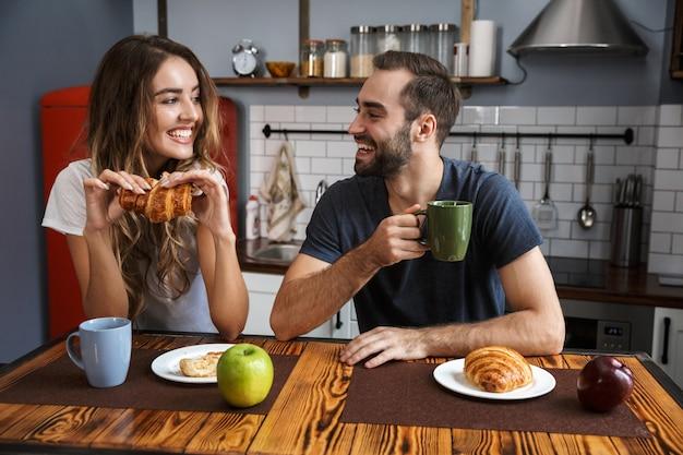 Retrato de pareja caucásica hombre y mujer comiendo croissants mientras desayuna en la cocina con estilo