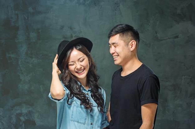 Retrato de pareja coreana sonriente en un estudio gris