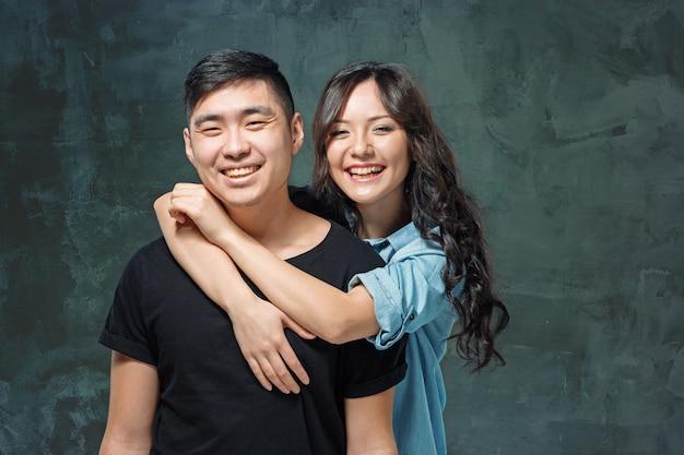Retrato de pareja coreana sonriente sobre un fondo gris de estudio