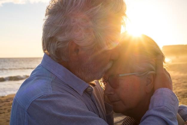 Retrato de pareja de dos personas mayores felices y maduros y ancianos en la playa juntos. pensionista y jubilado consolando triste esposa deprimida llorando.