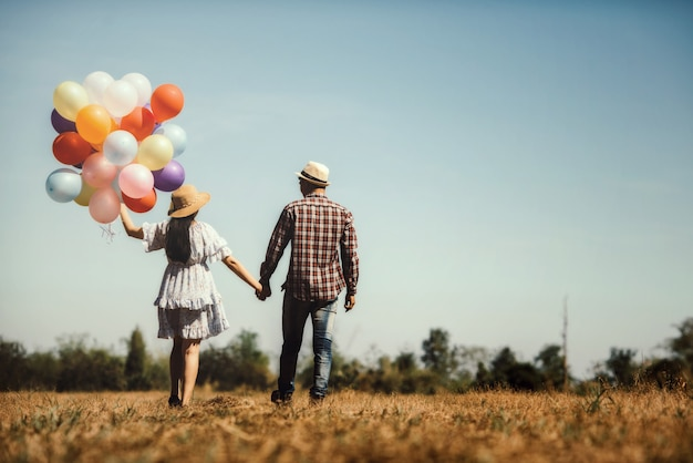 Retrato de una pareja enamorada caminando con globos de colores