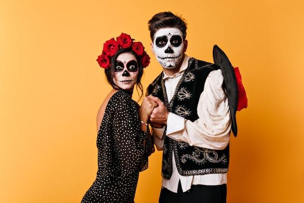 Retrato de pareja de enamorados en pared naranja aislada. chica y chico en forma de esqueletos se dan la mano con miedo