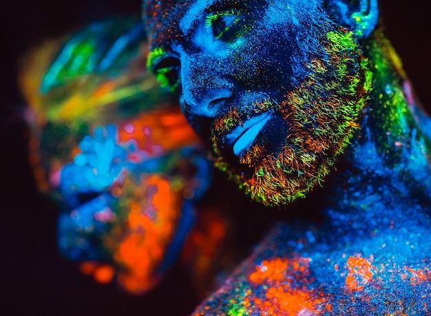 Retrato de una pareja de enamorados pintados en polvo fluorescente.