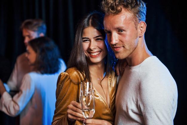Retrato de pareja encantadora tiene fiesta junto con sus amigos.
