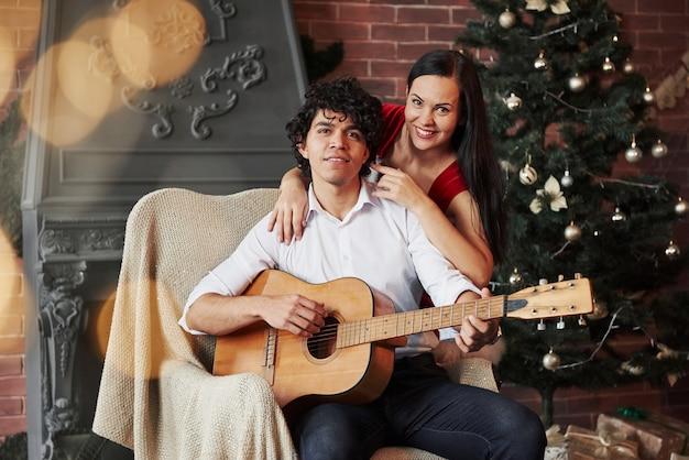 Retrato de una pareja encantadora en vacaciones. chico atractivo pelo rizado sentado en la silla con guitarra acústica con árbol de navidad detrás. novia con vestido blanco abraza a su novio