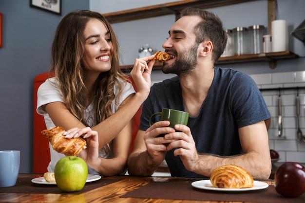 Retrato de pareja europea hombre y mujer comiendo croissants mientras desayuna en la cocina con estilo