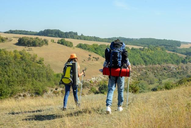 Retrato de pareja de excursionistas felices en el campo