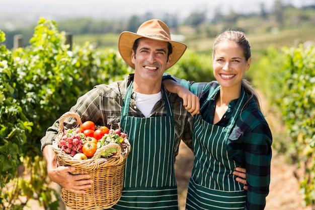 Retrato de pareja feliz agricultor sosteniendo una canasta de verduras