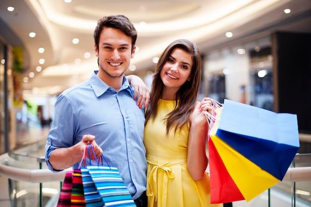Retrato de pareja feliz con bolsas de la compra.