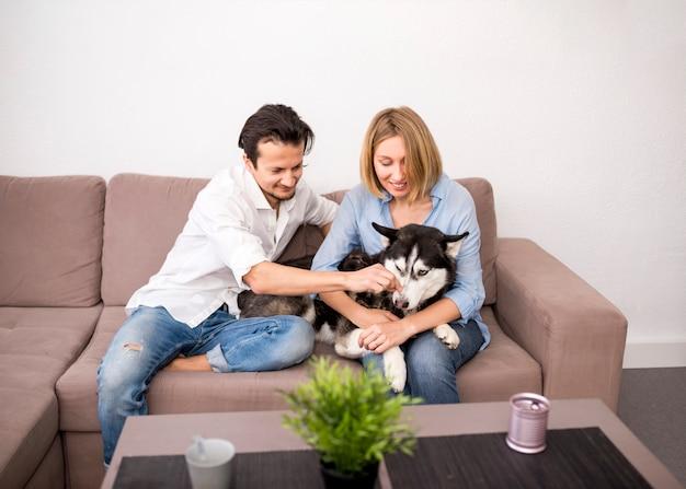 Retrato de pareja feliz en casa con perro