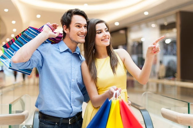 Retrato de pareja feliz en el centro comercial