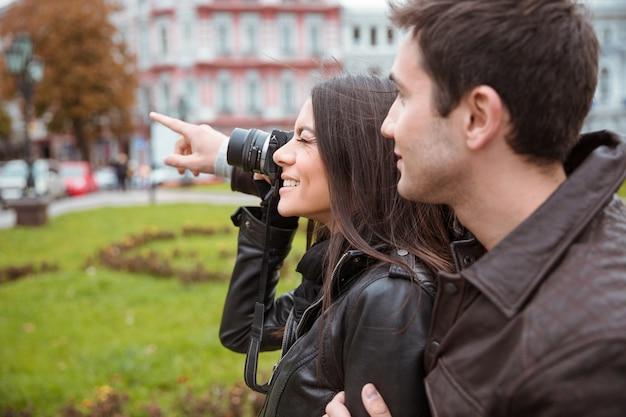 Retrato de una pareja feliz haciendo fotos en la parte delantera al aire libre