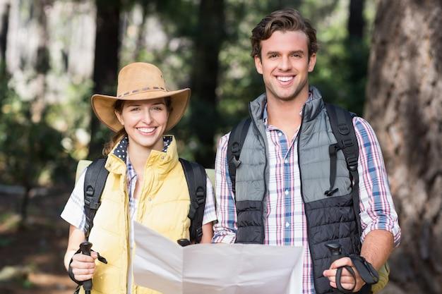 Retrato de una pareja feliz con el mapa durante el senderismo