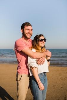 Retrato de una pareja feliz de pie cerca de la orilla del mar mirando a la playa