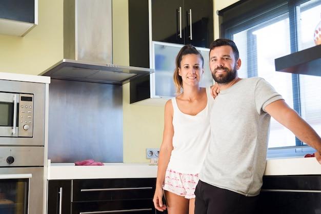 Retrato de una pareja feliz de pie en la cocina