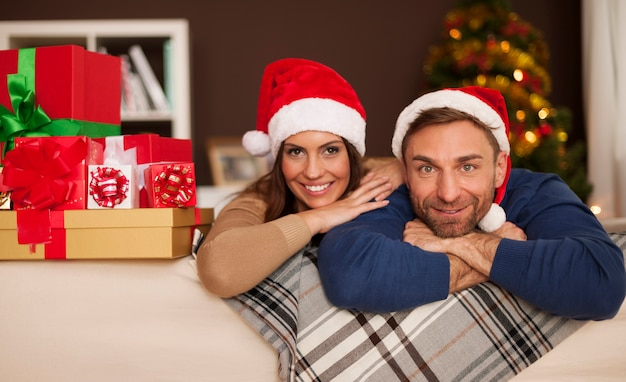 Retrato de pareja feliz en santa hat relajante en el sofá