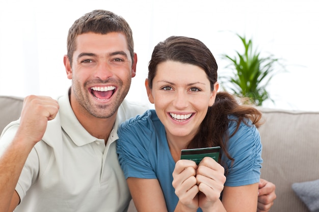 Retrato de una pareja feliz con su tarjeta de crédito en el sofá