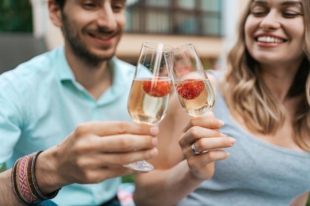 Retrato de pareja feliz tintineo de dos vasos con vino espumoso y fresas dentro con casa borrosa