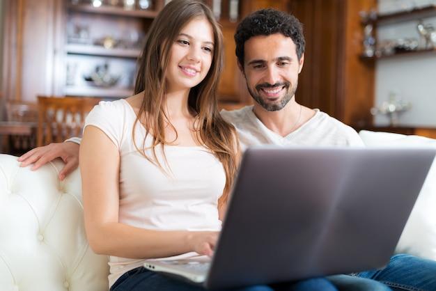 Retrato de una pareja feliz usando una computadora portátil en su casa.