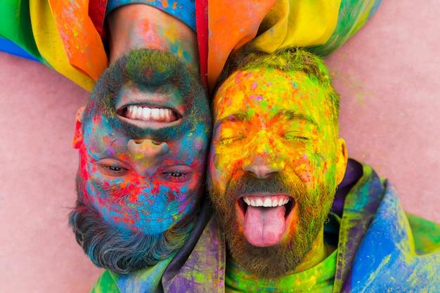 Retrato de pareja gay riendo manchada en pintura.