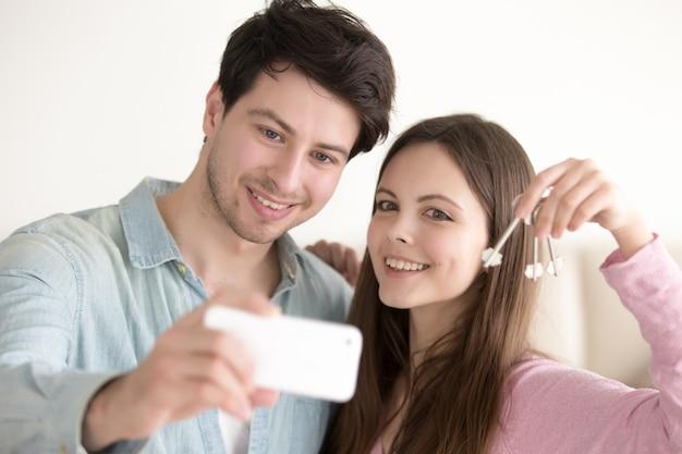 Retrato de una pareja hermosa haciendo selfie en móvil sosteniendo la llave