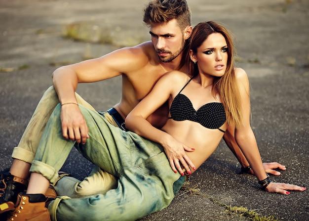 Retrato de pareja hermosa. modelo de mujer joven rubia elegante sexy con maquillaje brillante con piel bronceada perfecta y hombre musculoso guapo en jeans al aire libre sobre fondo de asfalto