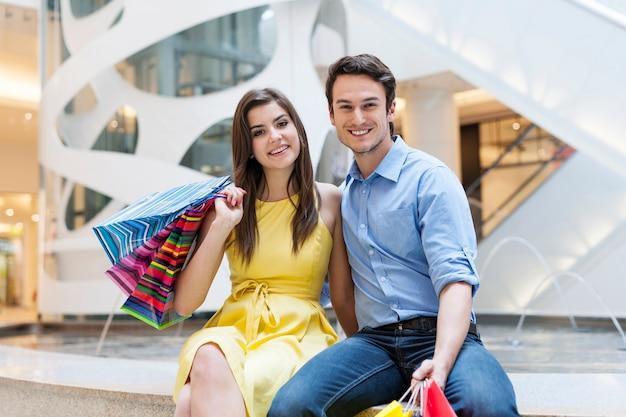 Retrato de pareja hermosa y sonriente en el centro comercial