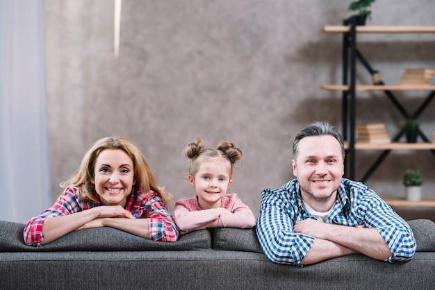 Retrato de la pareja y de la hija jovenes sonrientes que se sientan en el sofá