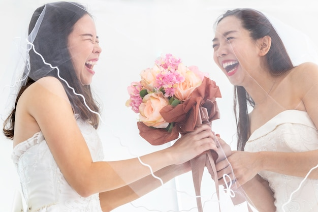 Retrato de pareja de homosexuales asiáticos sosteniendo flores en vestido de novia. concepto lgbt lesbiana.