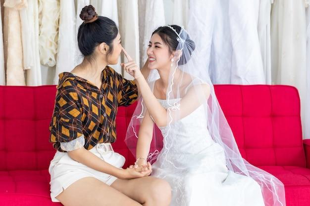 Retrato de pareja de homosexuales asiáticos en vestido de novia elegir vestido en una tienda. concepto lgbt lesbiana.