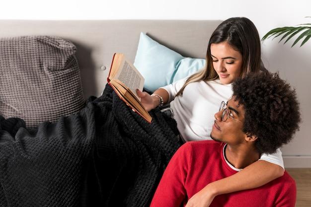 Retrato de pareja interracial leyendo juntos