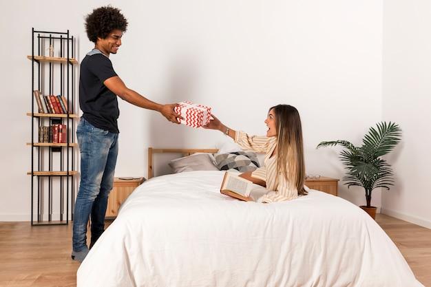 Retrato de pareja interracial con regalo