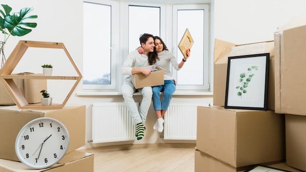 Retrato de una pareja joven amorosa sentada en el alféizar de la ventana en un nuevo apartamento mirando el marco