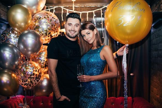 Retrato de pareja joven atractiva en el club con globo de aire