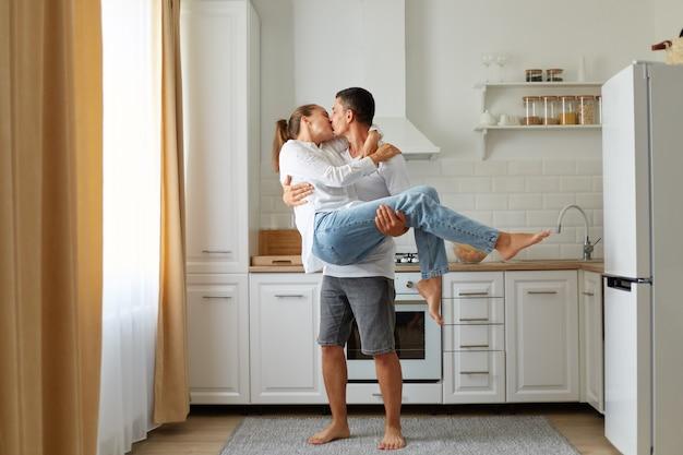 Retrato de pareja joven en una cocina acogedora, el chico y la chica se besan y abrazan, el hombre sostiene a una mujer en sus brazos, pasando tiempo juntos, luna de miel, sentimientos románticos.