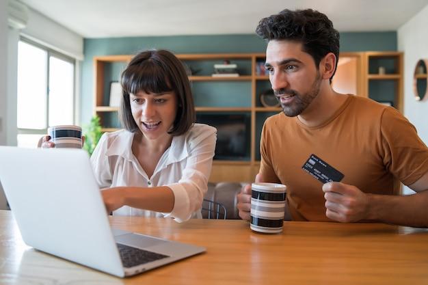 Retrato de pareja joven de compras en línea con una tarjeta de crédito y un portátil desde casa