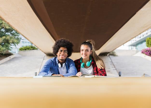 Retrato de una pareja joven diversa sentada bajo el puente estudiando juntos en el campus universitario