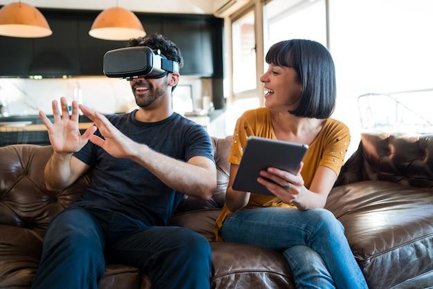 Retrato de pareja joven divirtiéndose juntos y jugando videojuegos con gafas vr mientras se queda en casa
