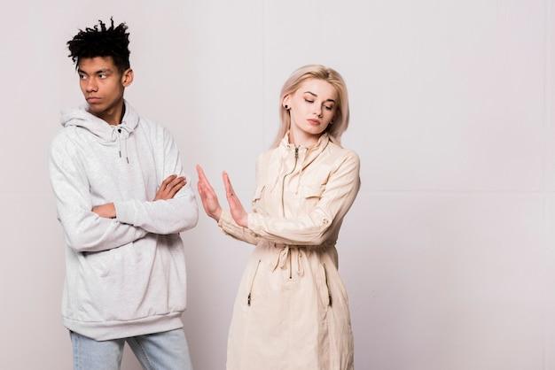 Retrato de pareja joven interracial ignorándose mutuamente contra el fondo blanco