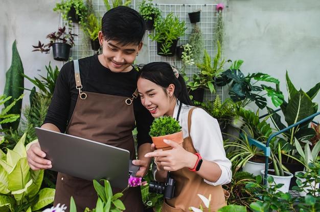 Retrato de pareja joven jardinero asiático con delantal utiliza equipo de jardín y computadora portátil para investigar y cuidar las plantas de la casa en invernadero