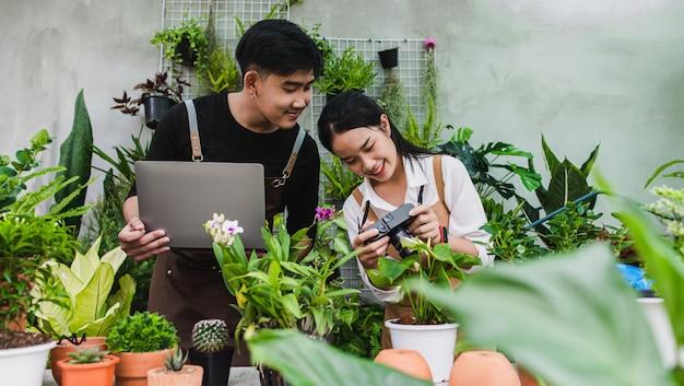 Retrato de pareja joven jardinero asiático vistiendo delantal usa computadora portátil y cámara para tomar una foto mientras cuida las plantas de la casa en invernadero
