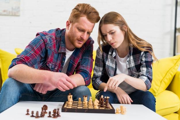 Retrato de una pareja joven jugando al ajedrez de madera juntos en casa